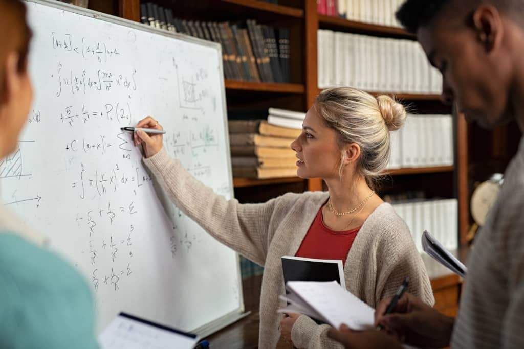 An online tutor explaining maths questions on white board to her students